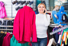 Girl selecting cardigan and chatting on the phone. Positive  girl selecting a sporty cardigan and chatting on the phone Royalty Free Stock Photos