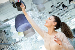 Girl selecting chandelier for interior Stock Images