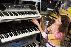 Girl selecting control keyboard. Happy girl selecting control keyboard for synthesiser in shop Stock Photography