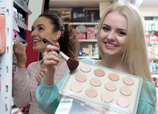 Girl selecting face powder. Young girl selecting face powder in beauty store and smiling royalty free stock photo