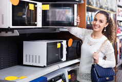 Girl selecting microwave oven Royalty Free Stock Photos
