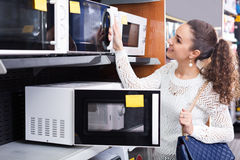 Girl selecting microwave oven Stock Photo