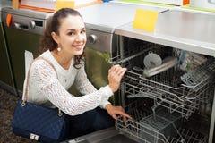 Girl selecting modern dishwasher. Pretty girl selecting modern dishwasher in hypermarket royalty free stock image