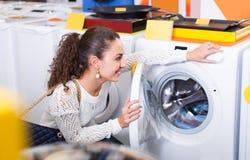 Girl selecting new washing machine. Joyful smiling brunette girl selecting washing machine in hypermarket Stock Image