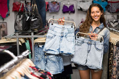 Girl selecting shorts in clothing store Royalty Free Stock Images