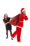 Girl selects bag with presents from santa Royalty Free Stock Photos