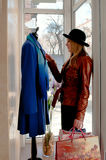 The girl selects a coat from shop Stock Image