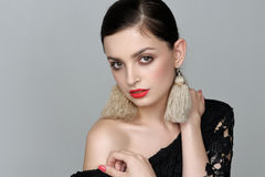 Girl with self-made earrings of threads, who bare her shoulder Royalty Free Stock Images