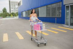 Girl with self-service supermarket full shopping trolley cart with fresh grocery products and blue handle. Royalty Free Stock Photo