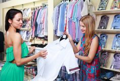 Girl seller helps shoppers Stock Images