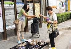 A girl selling crafts to a visitor Royalty Free Stock Photo