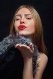 Girl send kiss. Luxury girl with fur send kiss on black background Stock Photos