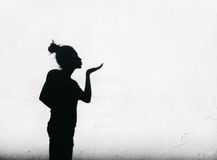 Girl sending air kiss around on white wall background Royalty Free Stock Images
