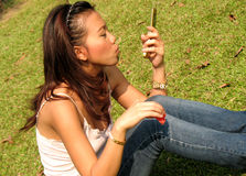 Girl sending kiss on mobile phone. Girl sitting in grass with mobile phone Stock Photos