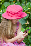 GIRL SENDING SMS. Little girl sending an sms dressed in pink hat and pink dress Stock Photo