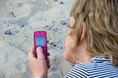 The girl sends sms. The girl sends love sms on a beach Royalty Free Stock Images