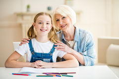 Girl and senior woman drawing together and smiling at camera Stock Images