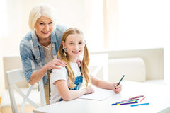 Girl and senior woman drawing together and smiling at camera Royalty Free Stock Photography