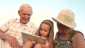 Girl with seniors using pc tablet. Caucasian little girl with gadget outdoors. The possibilities of modern technologies make life easier. Entertainment with stock footage