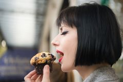 Girl with sensual face eat blueberry muffin in paris, france. Girl or woman with sensual face eat blueberry muffin in paris, france. Hunger, temptation, appetite Royalty Free Stock Photos