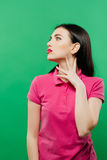 Girl with Sensual Red Lips and Long Dark Hair Posing on Green Background. Fashion Portrait of Young Woman with Bright Makeup Wearing Pink Clothes Royalty Free Stock Image
