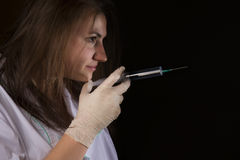 Girl sent a syringe Royalty Free Stock Images
