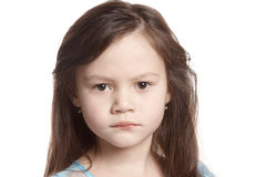 Girl with a serious face. Portrait of a little girl looking into the camera Stock Photos