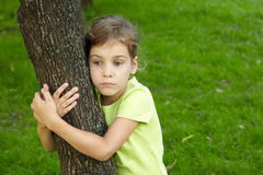 Girl with serious face stands, embracing tree Royalty Free Stock Photos