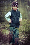 Girl seriously in a waistcoat in the woods. Cute girl seriously in a waistcoat in the woods Stock Photo