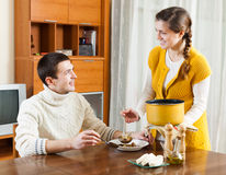 Girl serving soup her man Royalty Free Stock Photos