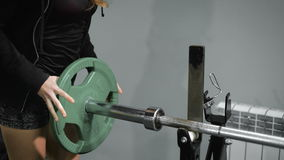 Girl sets weight plate on barbell. Slim girl places weight plate at the rod. Close-up of sport girl setting metal plate on barbell stock video