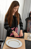 Girl setting  the table Stock Images