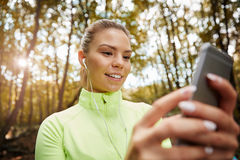 Girl setting up playlist for morning jogging Stock Images