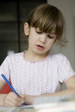 Girl seven years old doing homework Royalty Free Stock Images