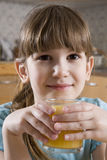 Girl seven years old drink orange juice. Little cute smiling girl seven years old drink orange juice royalty free stock photography