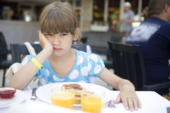 Girl seven years old eats a pancake Stock Images