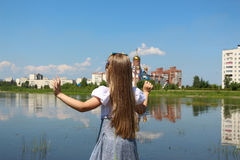 Girl seven years is streching out her hands and standing on the lakeshore. The Girl seven years in a homemade dress Royalty Free Stock Photo