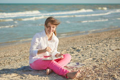Girl seventeen-year-old  with Down syndrome on the beach play wi Royalty Free Stock Photos