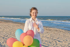 Girl seventeen-year-old with Down syndrome. Happy Girl seventeen-year-old with Down syndrome on the beach with balloons. Positive human emotions, feelings Royalty Free Stock Images