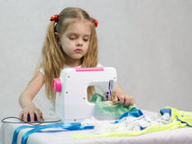 Girl sewing on the sewing machine Stock Photos