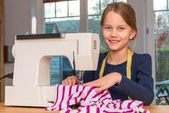 Free Girl Sewing A Pink And White Striped Cloth With A Sewing Machine Stock Photography - 108916142