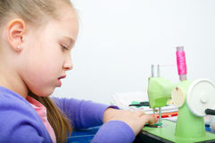 Girl sewing. Cute girl sewing on a sewing machine at home Royalty Free Stock Photography