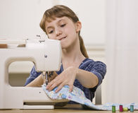 Girl on Sewing Machine Stock Photos