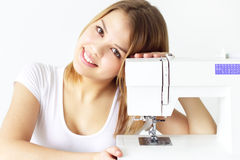 Girl with sewing machine Stock Images
