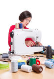 Girl at the sewing machine sews. Sewing Accessories Royalty Free Stock Photography