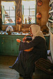 Girl sewing  in traditional clothes  at the gamle by of Ahrus Royalty Free Stock Photography