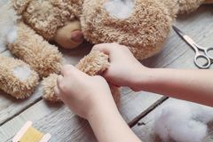 A girl sews a bear toy. Handicraft with children. Child fills the toy with a sintepon. A girl sews a bear toy. Handicraft with children. Child fills the toy Royalty Free Stock Photography