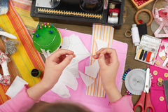Girl sews doll clothes, top view, sewing accessories top view, seamstress workplace, many object for needlework, handmade and hand. Icraft Stock Image