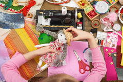 Girl sews doll clothes, top view, sewing accessories top view, seamstress workplace, many object for needlework, handmade and hand Royalty Free Stock Image