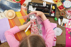 Girl sews doll clothes, top view, sewing accessories top view, seamstress workplace, many object for needlework, handmade and hand. Icraft Stock Photo